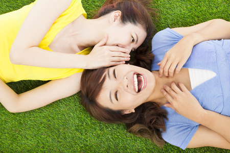 sisters whispering on the meadow and happy expression photo
