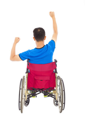 paralysis: handicapped man sitting on a wheelchair and fist pose