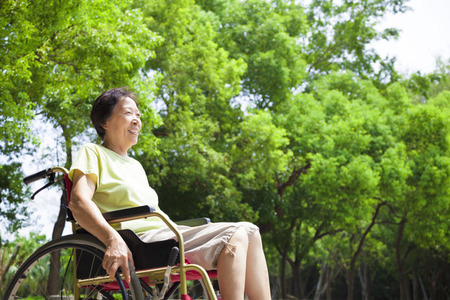 Asian senior woman sitting on a wheelchair in the park photo