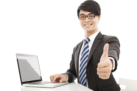 smiling  man using laptop and thumb up photo