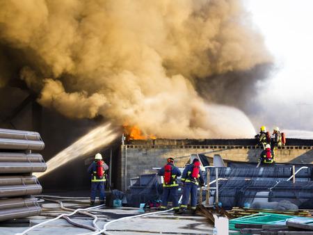 Plusieurs pompiers de soutien pour du feu de l'usine Banque d'images