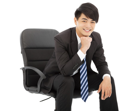 smiling Young businessman sitting on a chair photo