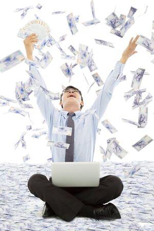 winning stock: business man winning a lottery with money rain background