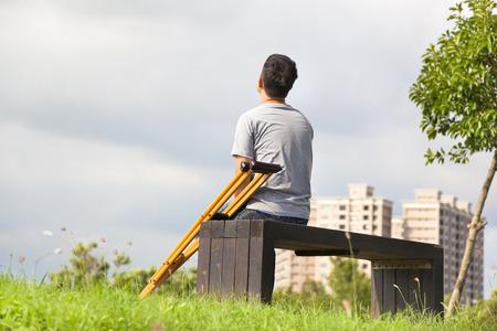 Gewonde man met krukken zit op een bankje