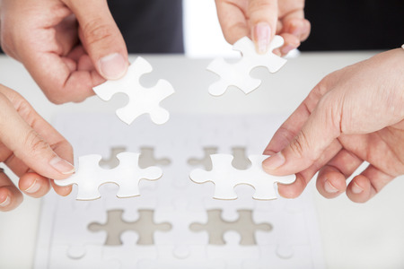 Business team Holding Jigsaw Puzzle on the desk photo