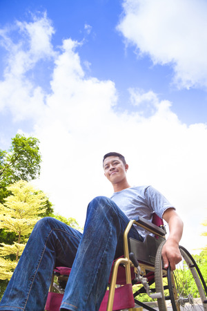 disability insurance: smiling young man sitting on a wheelchair with natural background Stock Photo