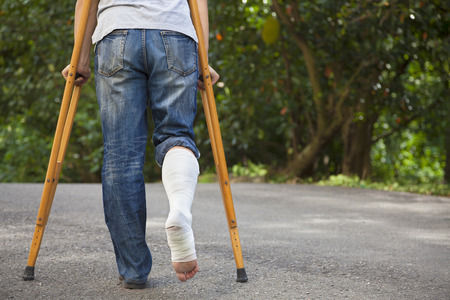 rehabilitation: Young asian man on crutches with tree background Stock Photo