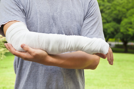 closeup of bandaged arm  with park background photo