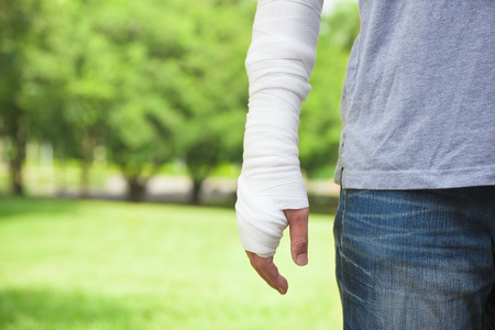 fracture arm: closeup of bandaged arm  with park background