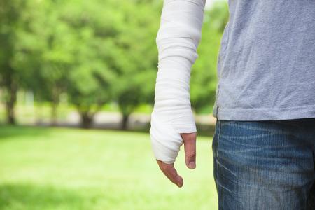 lesionado: primer plano de brazo vendado con el fondo del parque Foto de archivo