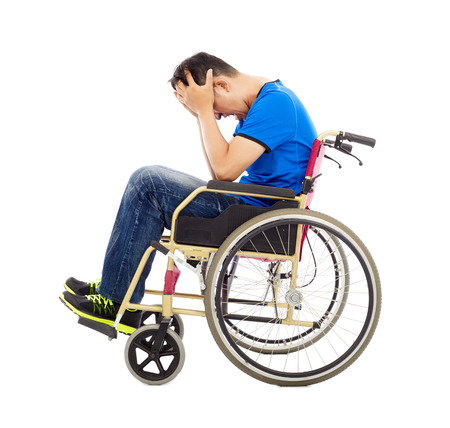 upset  and handicapped man sitting on a wheelchair  photo