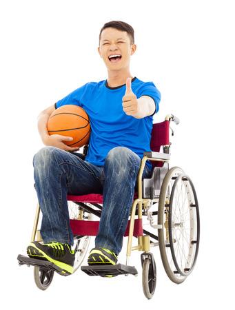innate: speranzoso giovane uomo seduto su una sedia a rotelle con un pallone da basket e pollice in su