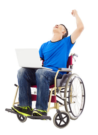 innate:  young man sitting on a wheelchair and  excited to raise arm Stock Photo