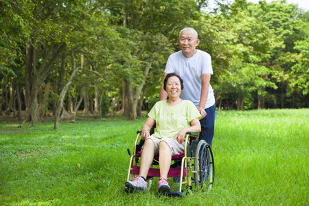 Asian senior woman sitting on a wheelchair with his husband photo