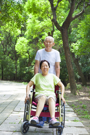 senior woman sitting on a wheelchair with his husband photo