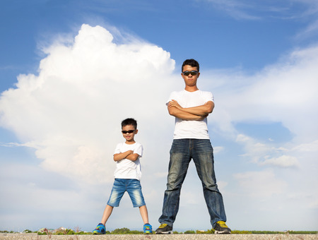 Asian father and son standing on a stone platform
