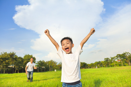 parent and child: feliz padre e hijo jugando en una pradera