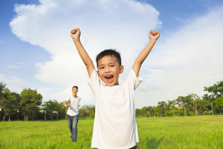 asian men: happy father and son playing in meadow Stock Photo
