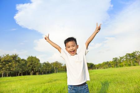 niños jugando en el parque: los niños felices de pie en la pradera y levantar las manos