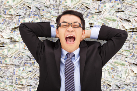 winning stock: happy young business man lying on the us dollar Stock Photo