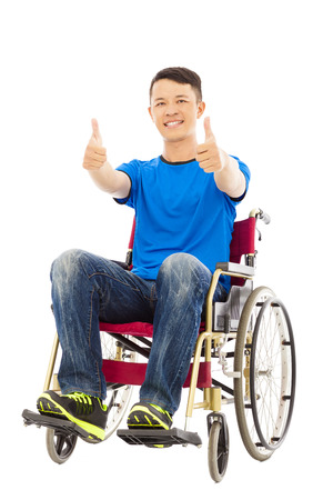 innate: happy young man sitting on a wheelchair and thumb up Stock Photo