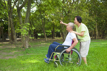 asian wife: Asian senior man sitting on a wheelchair with his wife Stock Photo