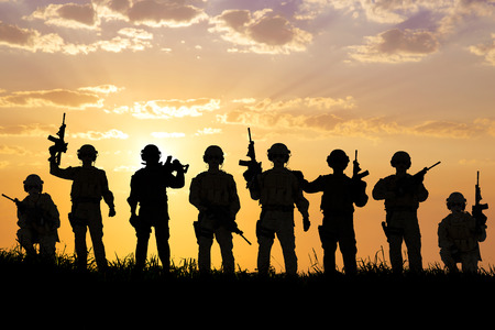 conflict: silhouette of  Soldiers team with sunrise background