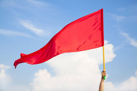 red hand: Hand waving a red flag with blue sky background  Stock Photo