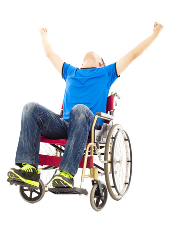 innate: excited young man sitting on a wheelchair and raising hands