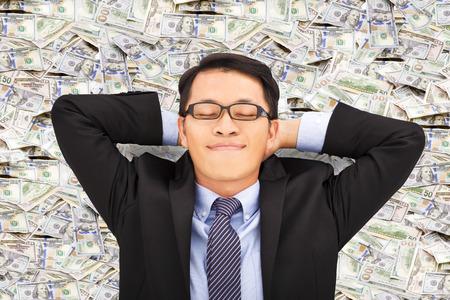 ビジネスの男性を楽しむとお金の上に横たわる 写真素材