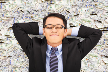 win money: business man enjoying and lying on the money Stock Photo