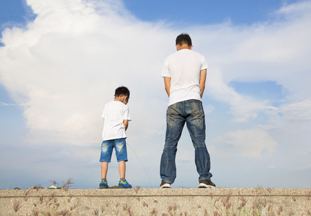 father and son standing on a stone platform and pee together  photo