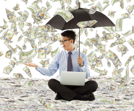 win money: young business man holding a umbrella with dollar rain