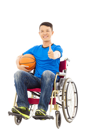 innate: asia young man sitting on a wheelchair and thumb up with a basketball Stock Photo