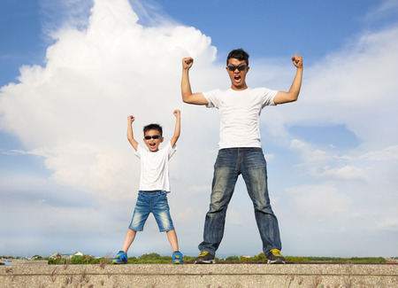 father and son standing  and raising hands   Stock Photo