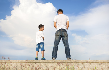 urinate: father and son standing on a stone platform and pee together