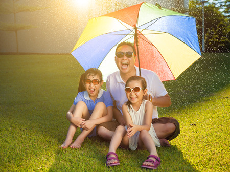 Father and daughters sitting on a meadow with colorful umbrella Stock Photo