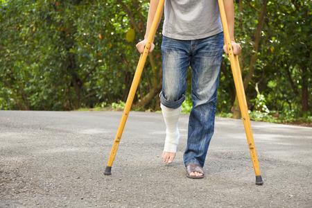 松葉杖で包帯の上に脚のクローズ アップ