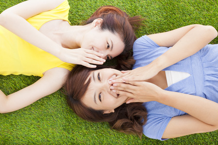 two asian sisters whispering gossip on the grass Stock Photo