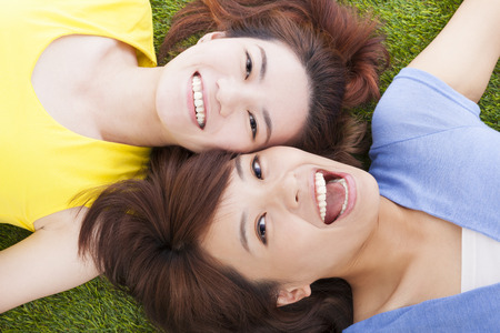 two asian pleasure young woman lying on grass photo