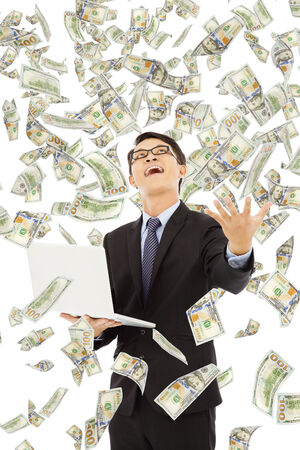 aisa: happy business man holding a laptop with money rain