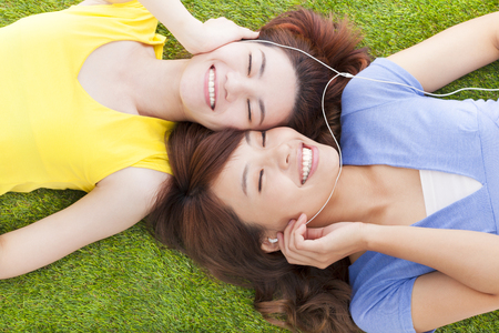 two pretty young woman lying on grassland and listening music  photo