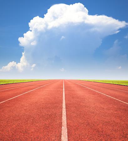 carrera de relevos: pista roja en el cielo azul y las nubes