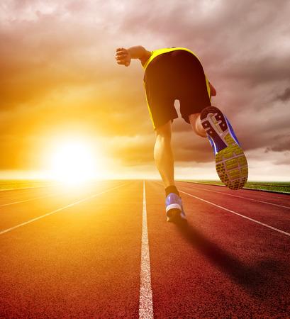 bieżnia: Athletic młody człowiek działa na torze z zachodem słońca
