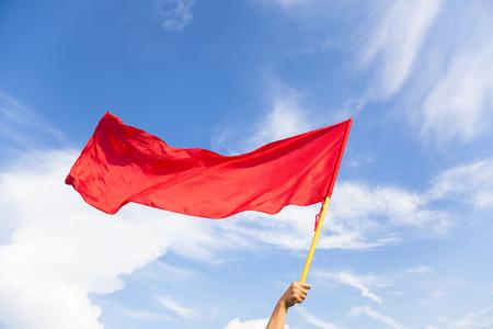 Mano que agita una bandera roja con el cielo azul Foto de archivo