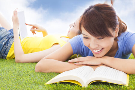 smiling pretty students lying on the grassland with books photo