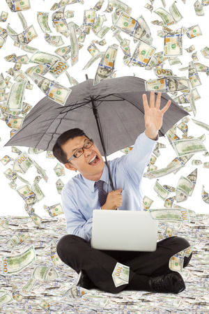 aisa: happy business man holding a umbrella and catching money