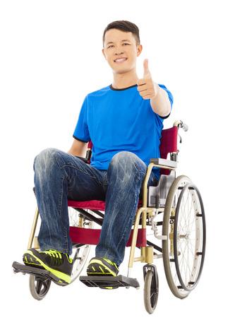 Gelukkig jonge man zit op een rolstoel en duim omhoog