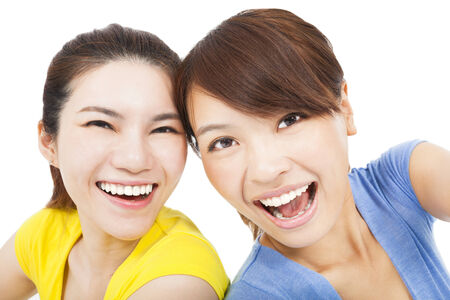 Closeup portrait of happy young girls over white  photo