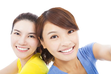 closeup of two happy young girls over white  photo